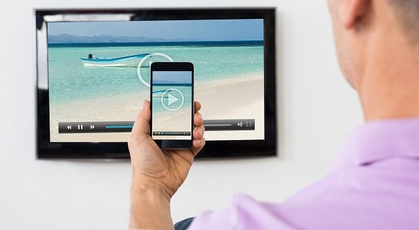 Man With Smartphone Connected To A TV Watching Video