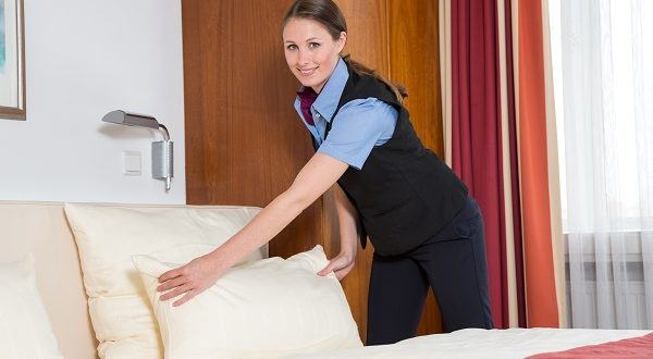 Maid making the bed in a hotel room