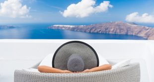 Travel vacation woman relaxing enjoying Santorini looking at famous view of Caldera. Young lady lying down on sun bed sofa lounge chair on holidays. Amazing view of sea. Europe travel destination.